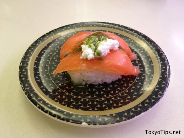 This is two salmon sushi with mozzarella cheese and basil.