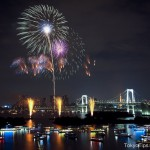 A Fireworks Festival at Tokyo Bay. Rainbow Bridge and Many Japanese style boats are.